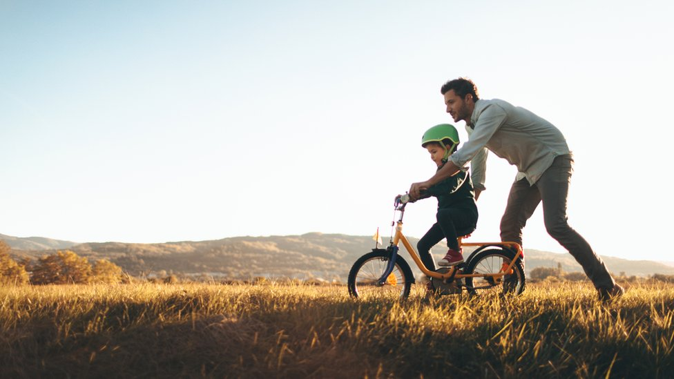 Padre ayuda a hijo a montar en bicicleta.