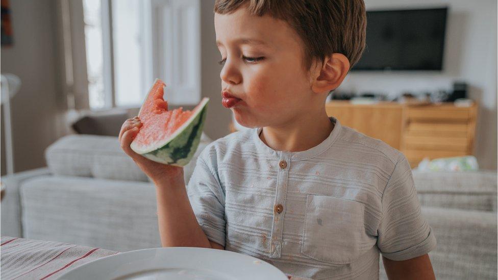 Niño comiendo sandía.