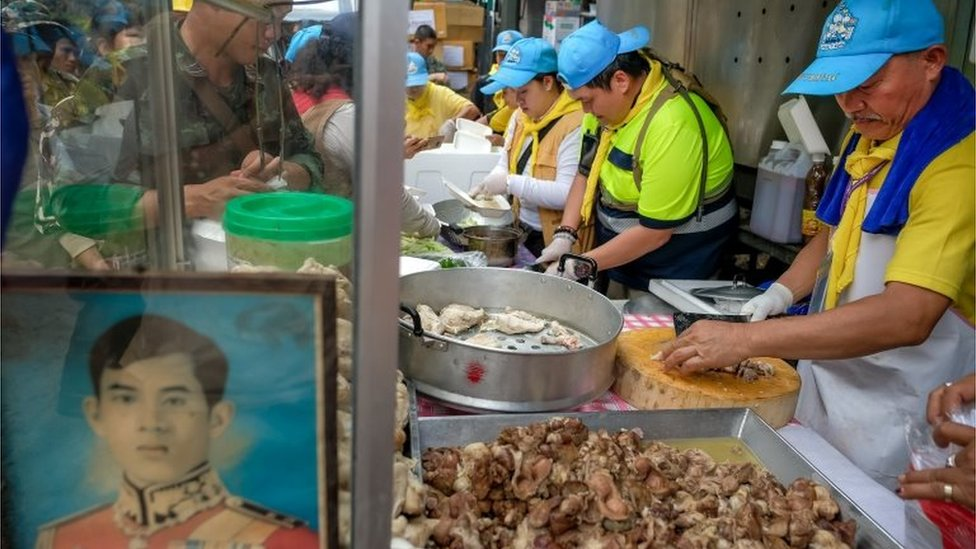 Volunteers prepare food for rescuers and family members outside the caves in Thailand on 5 July 2018