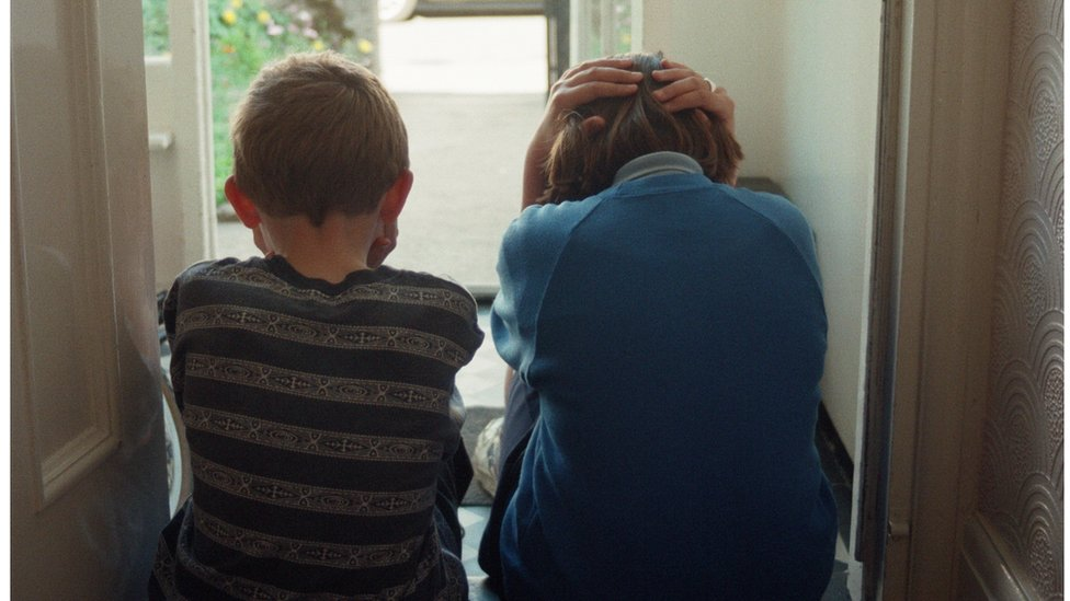 Children sitting on a porch with their backs turned to the camera