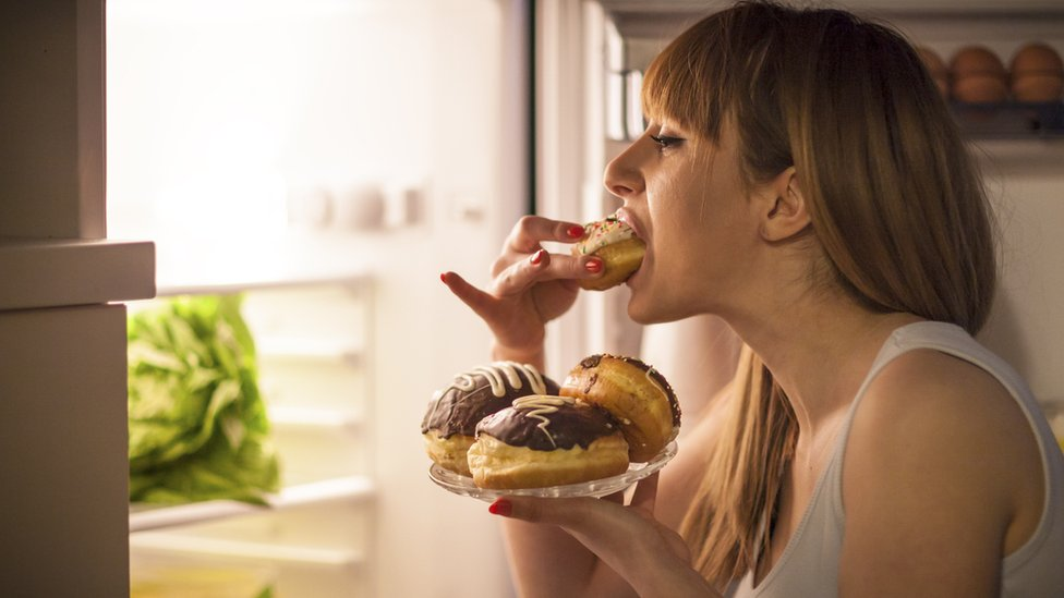 Mujer comiendo dulces en frente de la nevera.