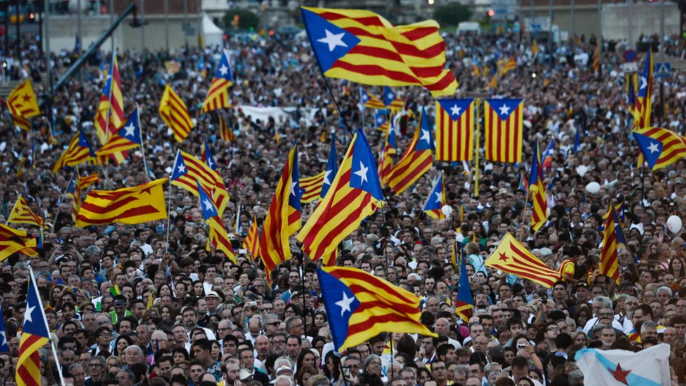 """This file photo taken on September 25, 2015 shows people waving Catalan and Catalan independence flags (Estelada) during the Catalan independence coalition """"Junts pel Si"""" (Together for the Yes) party""""s final campaign meeting for the regional election, in Barcelona."""