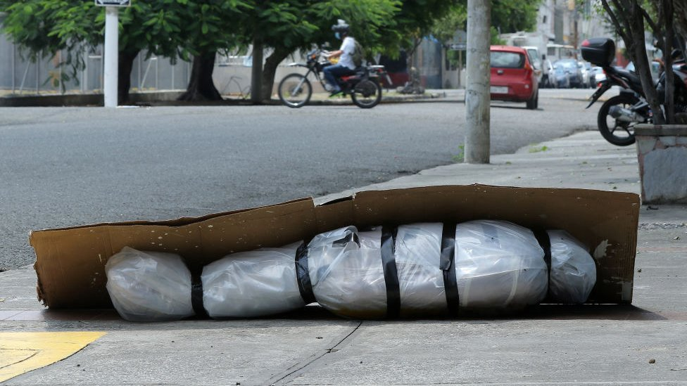 Cadáver envuelto en plástico en medio sobre una acera de Guayaquil.