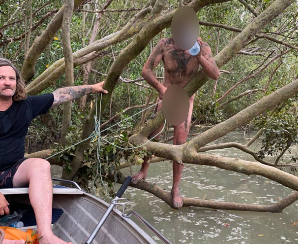 A fugitive who was found clinging to mangroves near Darwin, Australia drinks a bottle of water