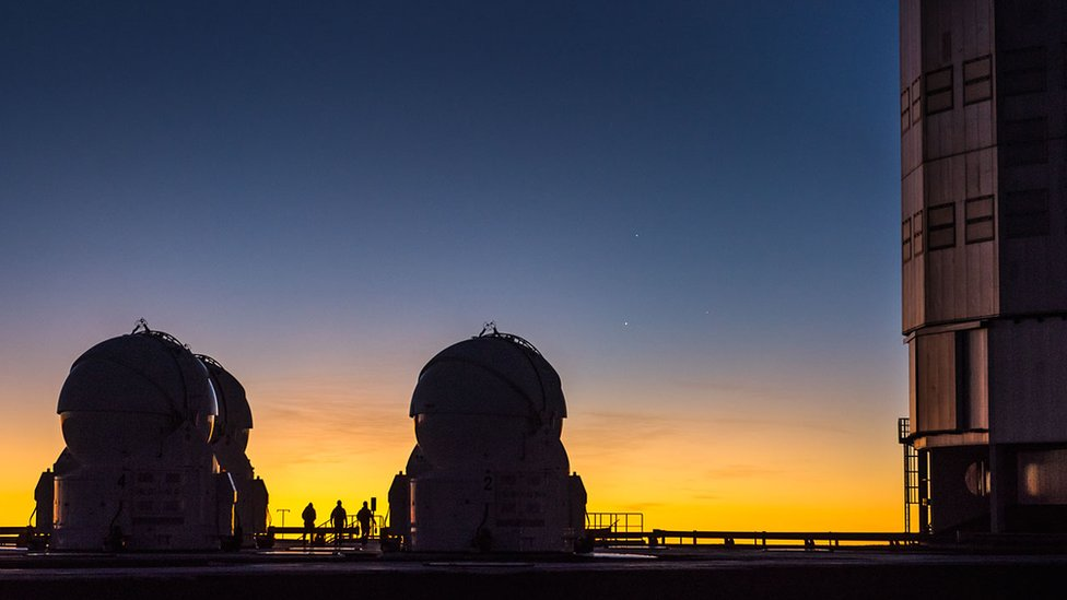 Three people standing between two large telescopes, behind three planets are visible in the night sky
