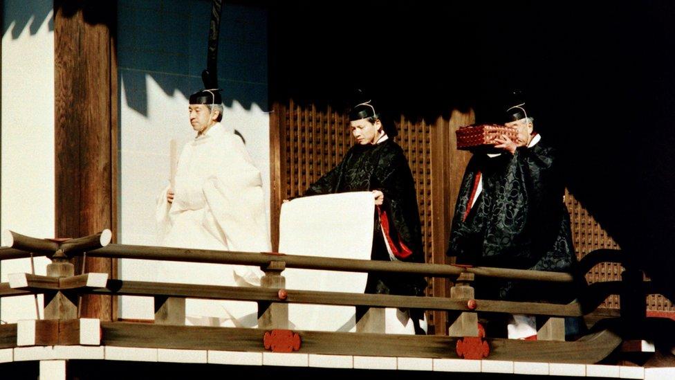 Kaisar Akihito diikuti pendeta Shinto yang membawa Harta Karun Kekaisaran di istana (1990).