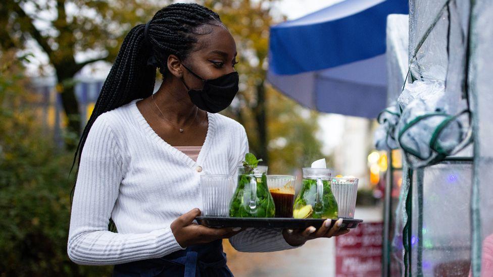 Garçonete de máscara segurando bandeja com bebidas