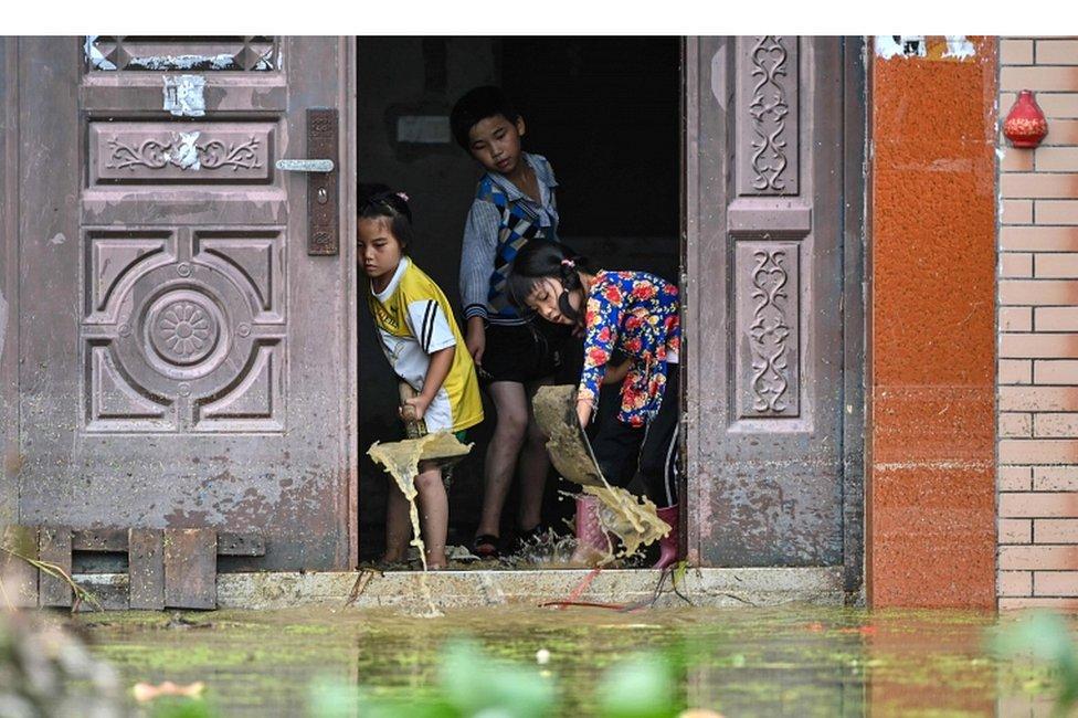 Deca izbacuju vodu iz porodične kuće u selu Longkou, koje je poplavljeno zbog velikih kiša, 16. jul 2020.