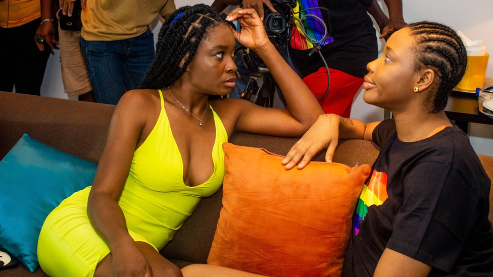 Two actors on the set of Ife are sat on a couch