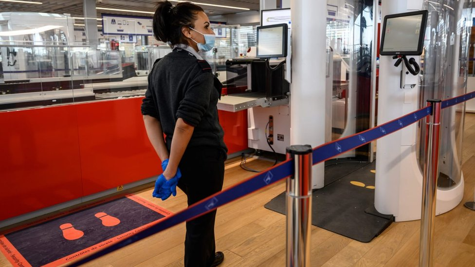 covid19, An airport staff member wearing protective face mask stands next to a body scanner in the boarding area of the Terminal 3 at Orly airport