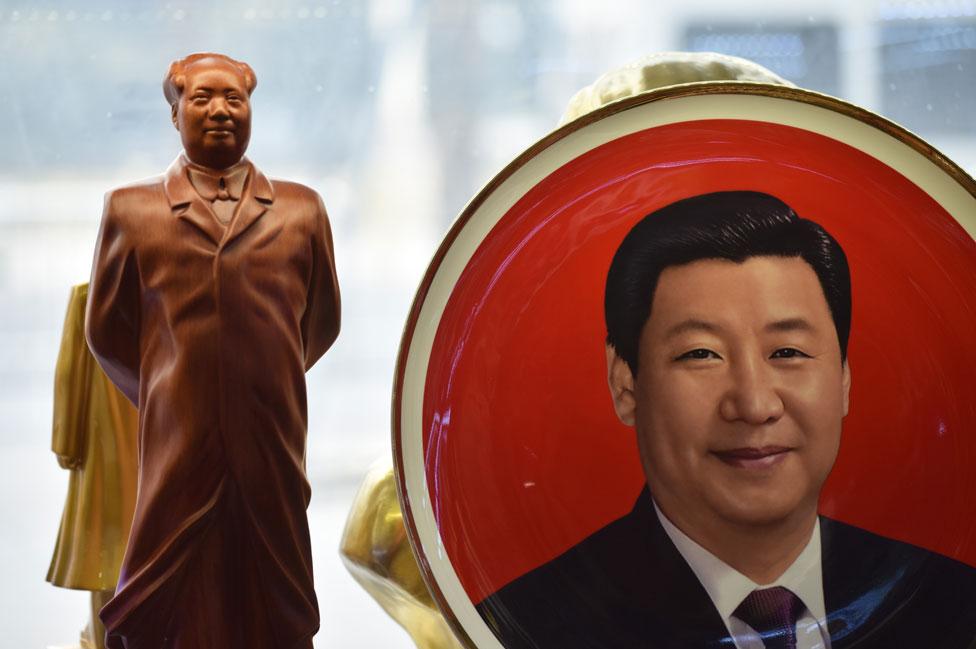 Un plato decorado con la imagen de Xi Jinping al lado de una estatuilla de Mao