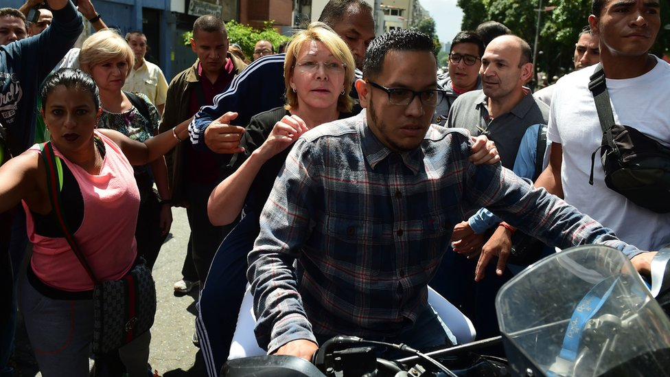 Venezuela's chief prosecutor Luisa Ortega is seen on a motorbike during a flash visit to the Public Prosecutor's office in Caracas