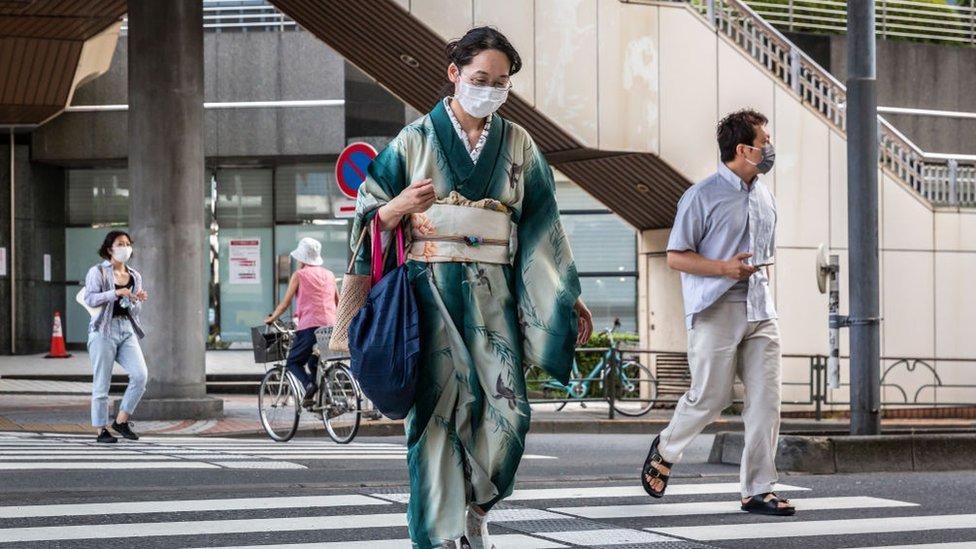 Mulher nas ruas com máscara