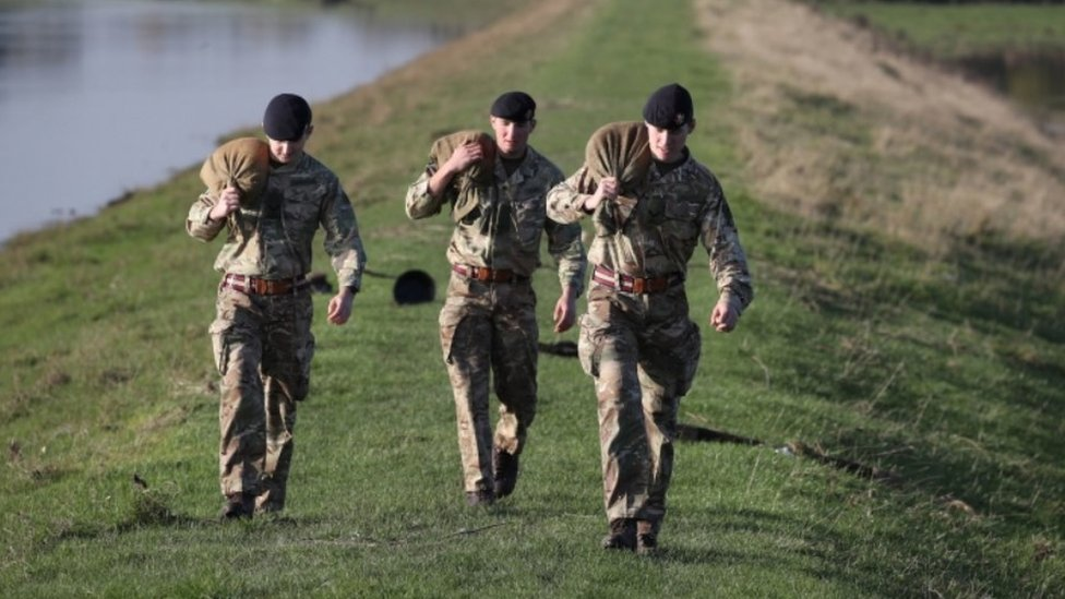 British Army soldiers carry sandbags in Stainforth