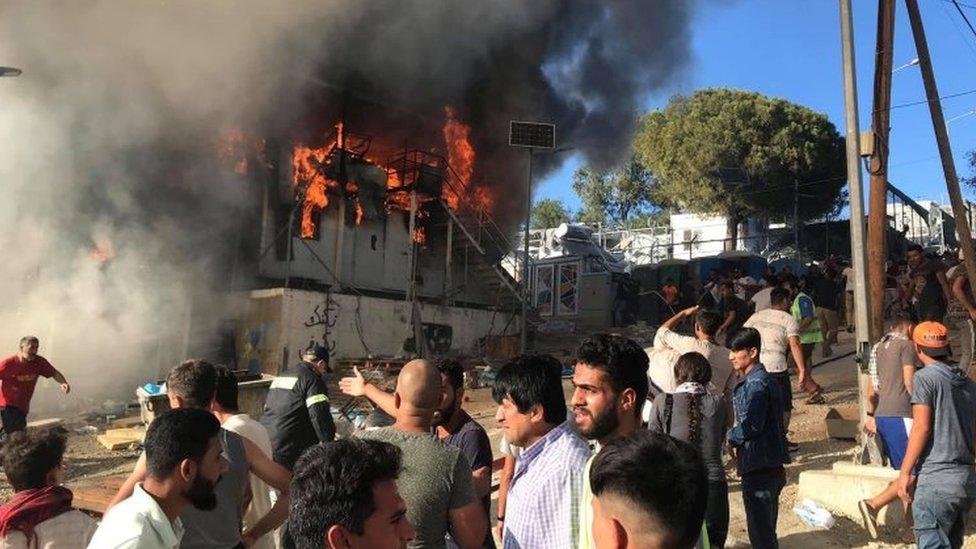 Ljudi stoje ispred zapaljenog kontejnera u Moria izbegličkom kampu na Lezbosu u Grčkoj