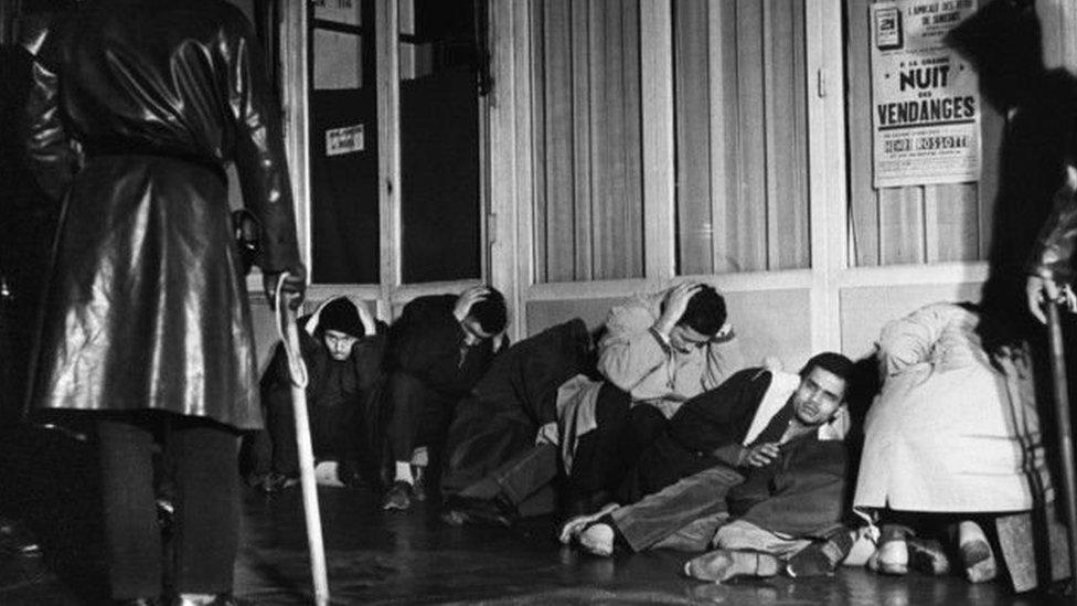 جزائريون على الأرض في قبضة الشرطة الفرنسية