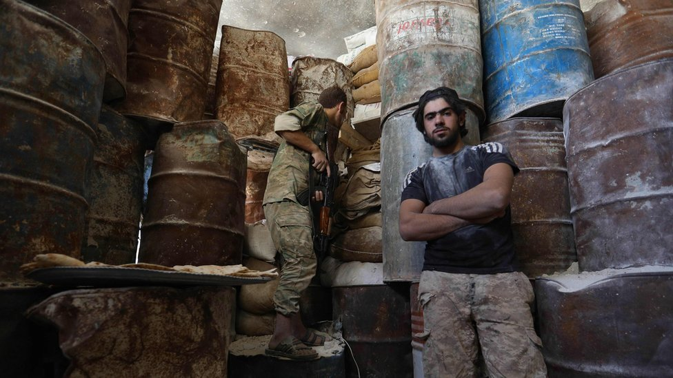 Syrian rebel fighters stand next to an improvised barricade in the western outskirts of Aleppo (10 September 2018)