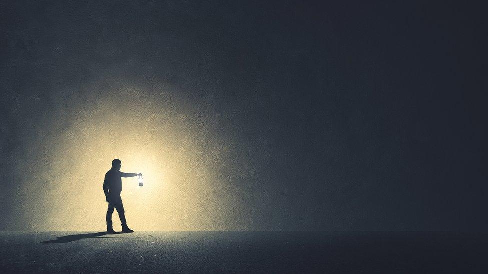 Hombre en la oscuridad con lámpara