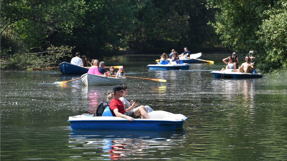 People enjoy hot weather on the boating lake in Victoria Park, London