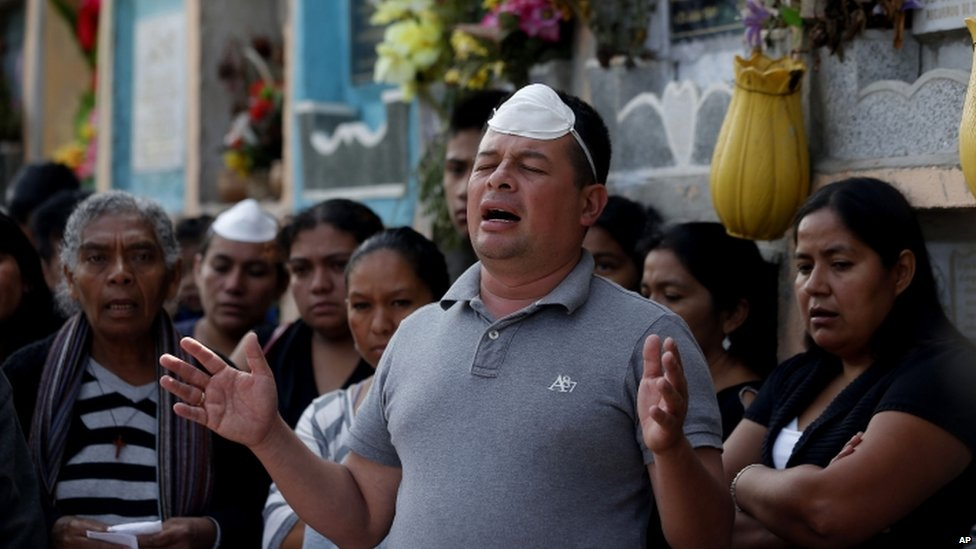 A man prays during the burial of five mudslide victims at the Santa Catarina Pinula cemetery