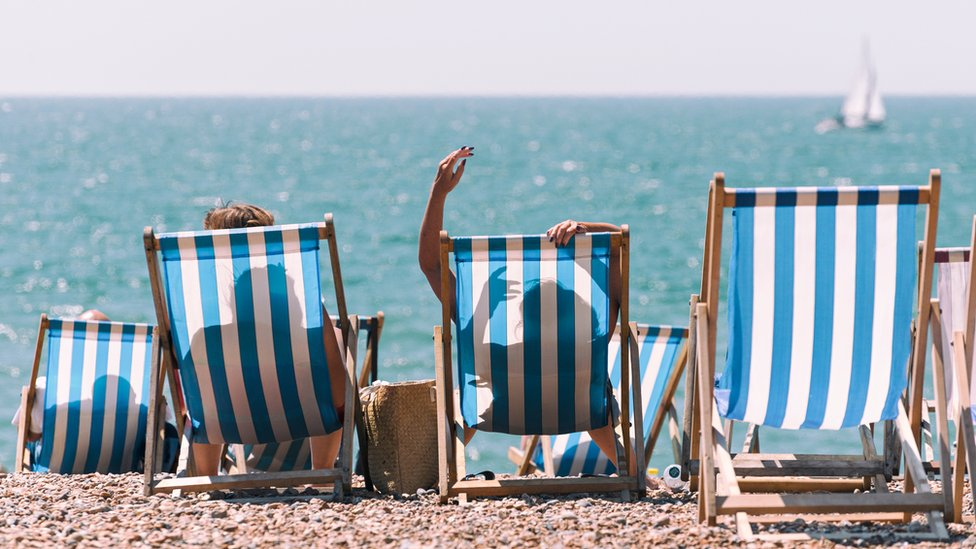 Bañistas sentados frente a la playa