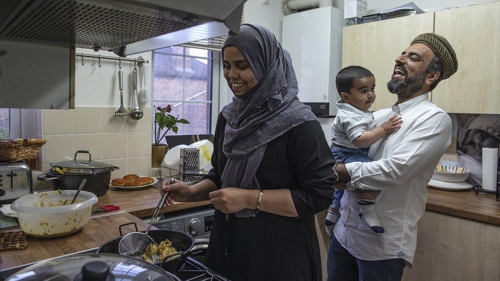 Imam Raza Ahmed holds his son as his wife prepares food for iftar