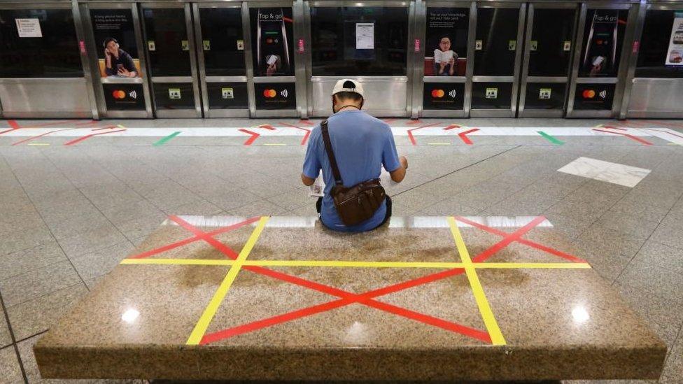 Hombre leyendo el periódico en una estación de trenes