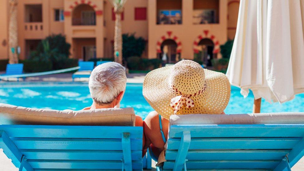 Pareja adulta frente a la piscina de un hotel
