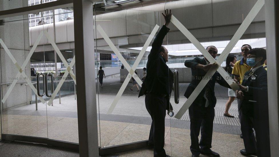 強烈熱帶風暴苗柏迫近香港之際中環國際金融中心物業管理人員為購物商場進出口玻璃門粘貼膠紙(12/6/2017)