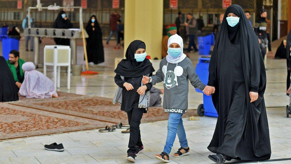 طفلان وامرأة يلبسون كمامات ويمسكوا أيديهم