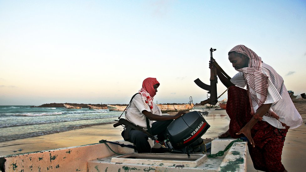 Somali men with guns getting aboard a small boat