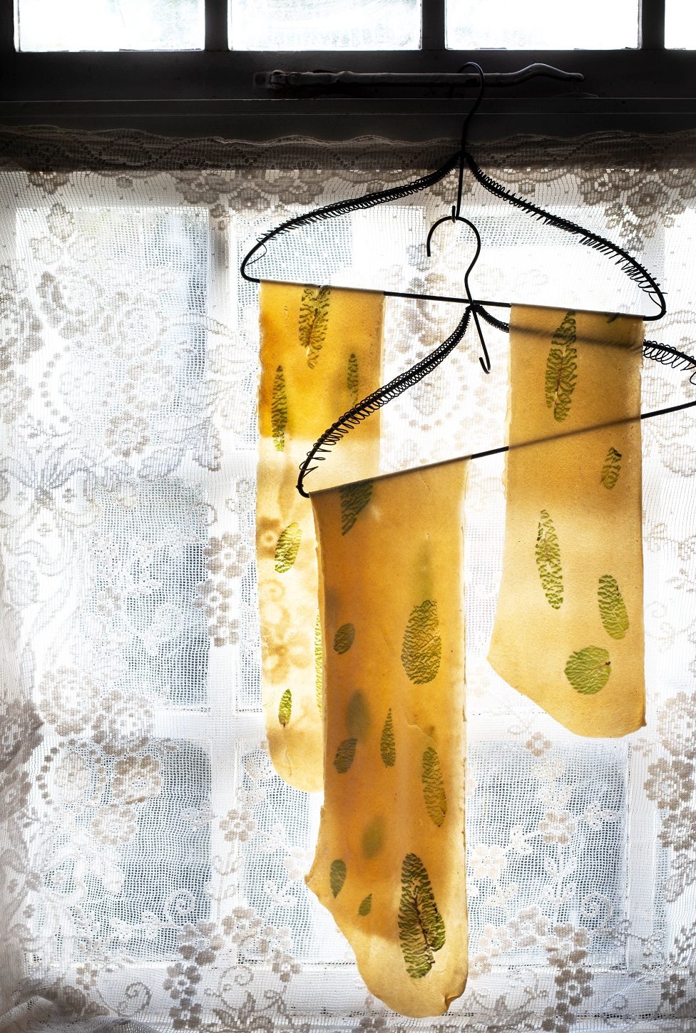 Sheets of pasta hanging to dry next to a window