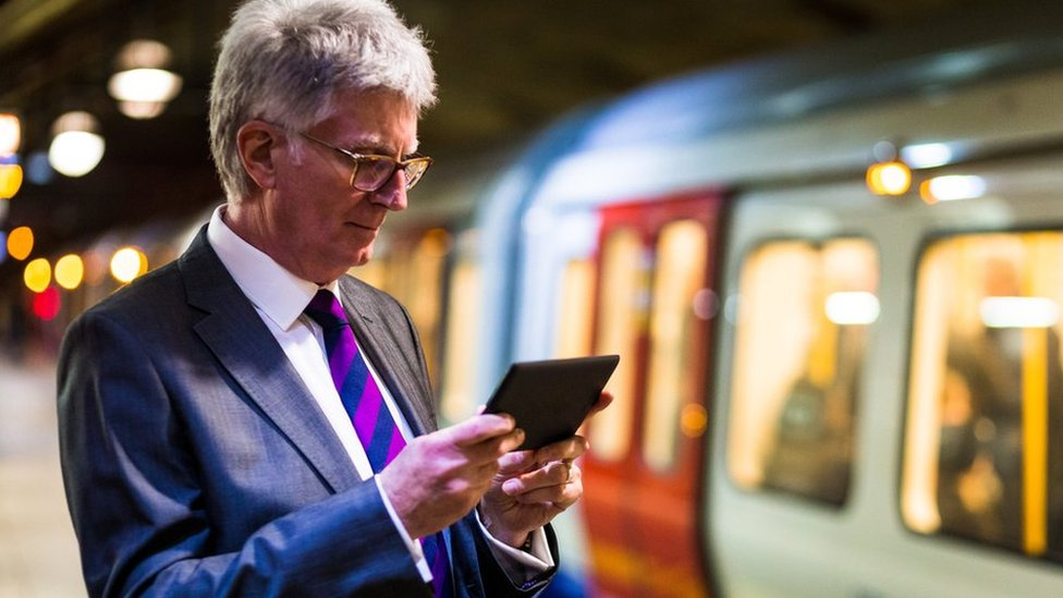 Man using mobile device on the Tube
