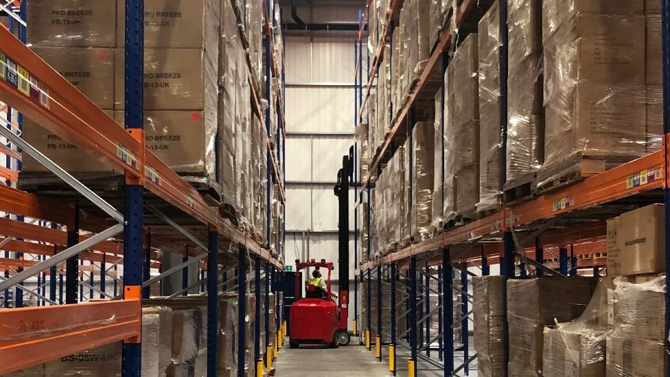 Boxes stocked high in a warehouse