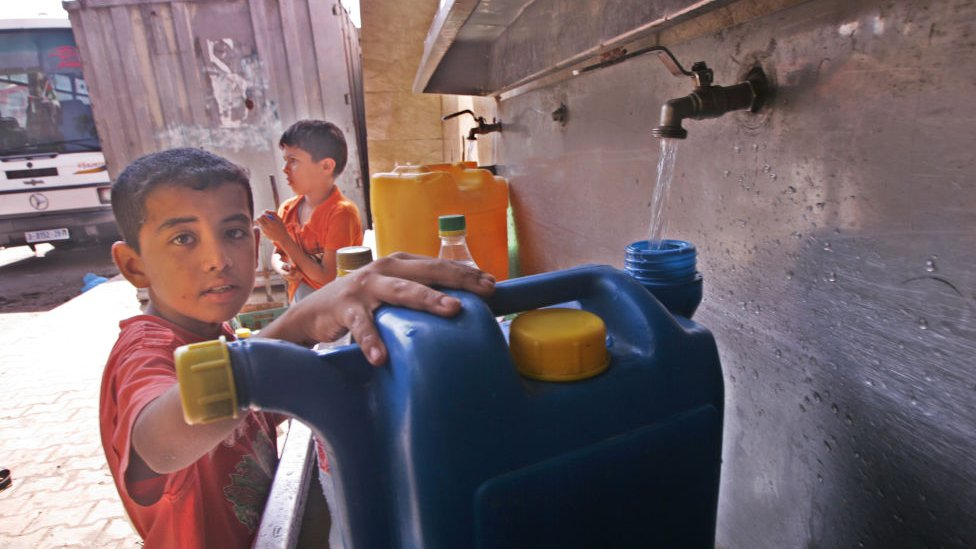 A Palestinian boy pours water into a container from a desalination plant