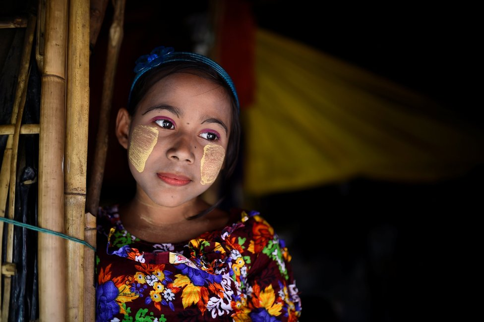Rohingya refugee Romzida, aged 8, poses for a photograph as she wears thanaka paste at Shamlapur camp in Cox's Bazaar, Bangladesh