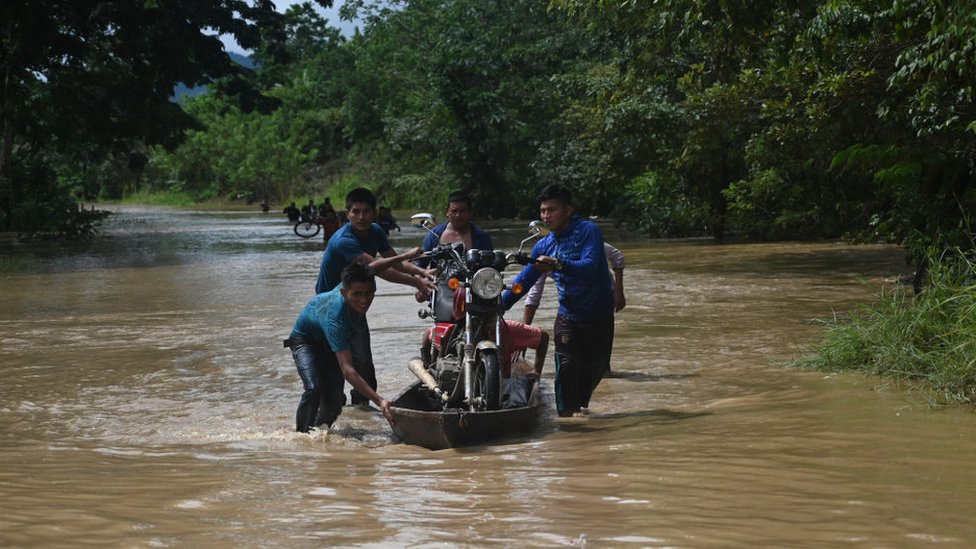People carry a motorbicycle on a boat in a flooded area in Panzos, Alta Verapaz
