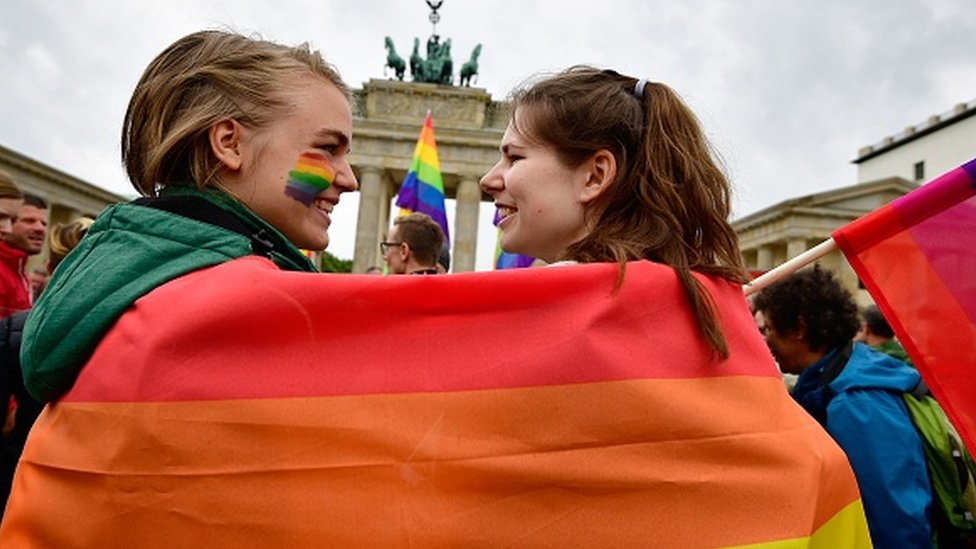 Two women are wrapped into a rainbow flag as they attend an LGBT rally in Berlin