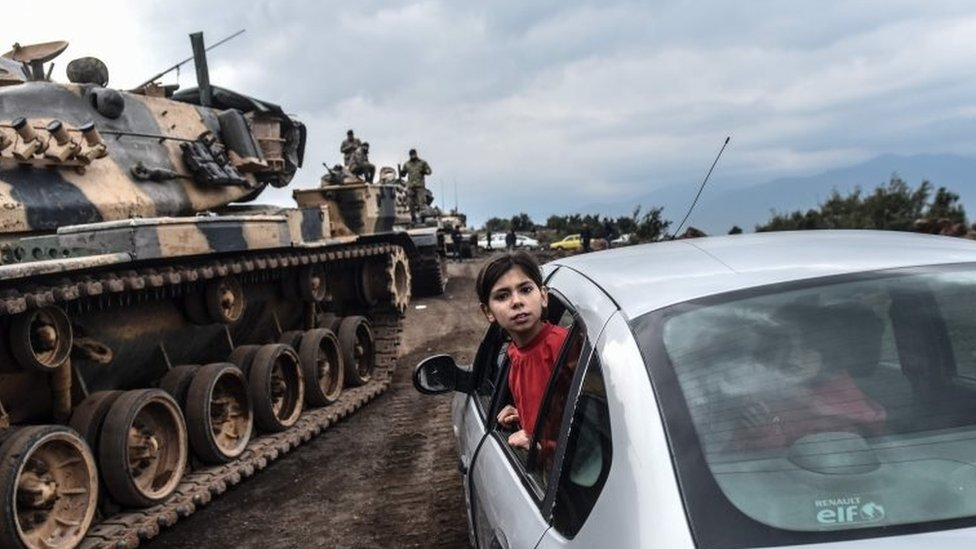 A Turkish girl leans out of a car window to have a look as Turkish army tanks and soldiers gather close to the Syrian border at Hassa, in Hatay province on 21 January 2018.