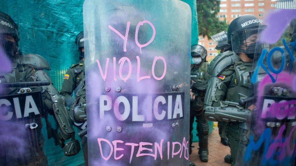 """Un policía sostiene un escudo en le que manifestantes escribieron """"""""yo violo detenidas""""."""