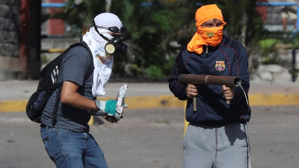 Protesters throw projectiles at military police officers during clashes, in Tegucigalpa