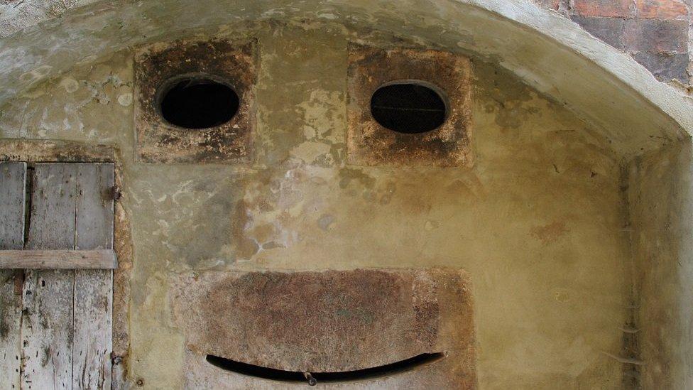 Una pared en Italia con aberturas que recuerdan a un rostro sonriente