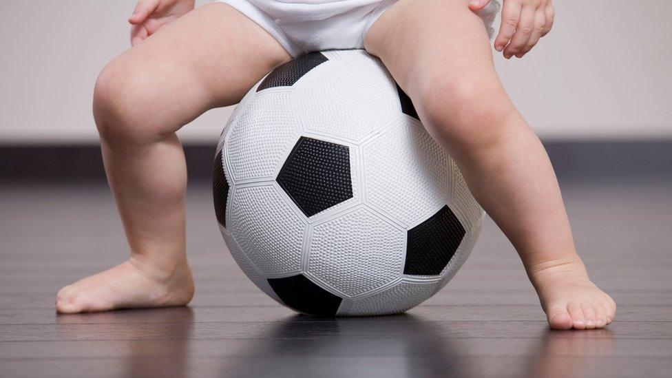 طفل يجلس على كرة