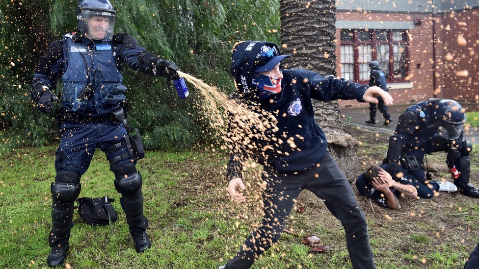 A policeman uses pepper spray towards a protester during clashes in the Melbourne suburb of Coburg, Australia, 28 May 28.