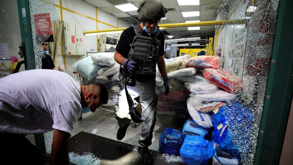 Israeli security personnel inspect a showcase damaged by a missile attack on the Israeli city of Ashdod (September 15, 2020)