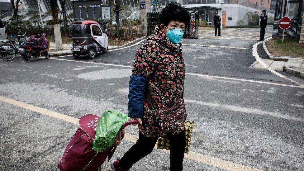 Una mujer usa una mascarilla mientras camina por la calle en Wuhan.