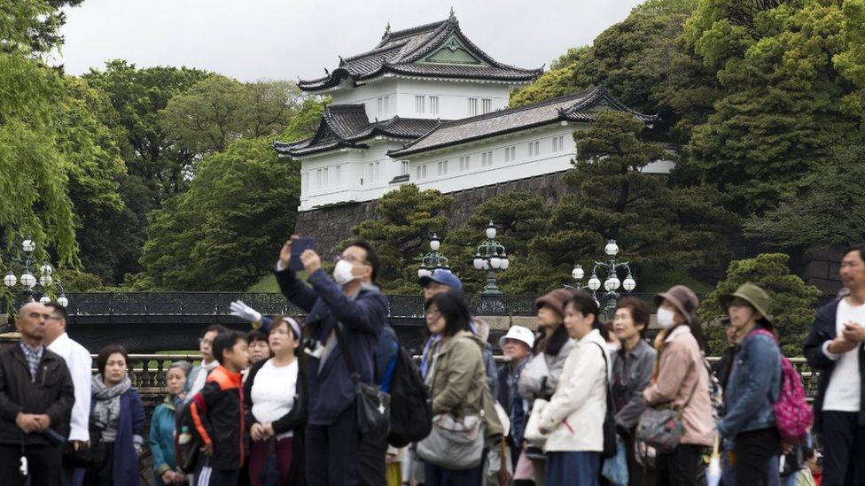Gente a las afueras del palacio imperial de Tokio