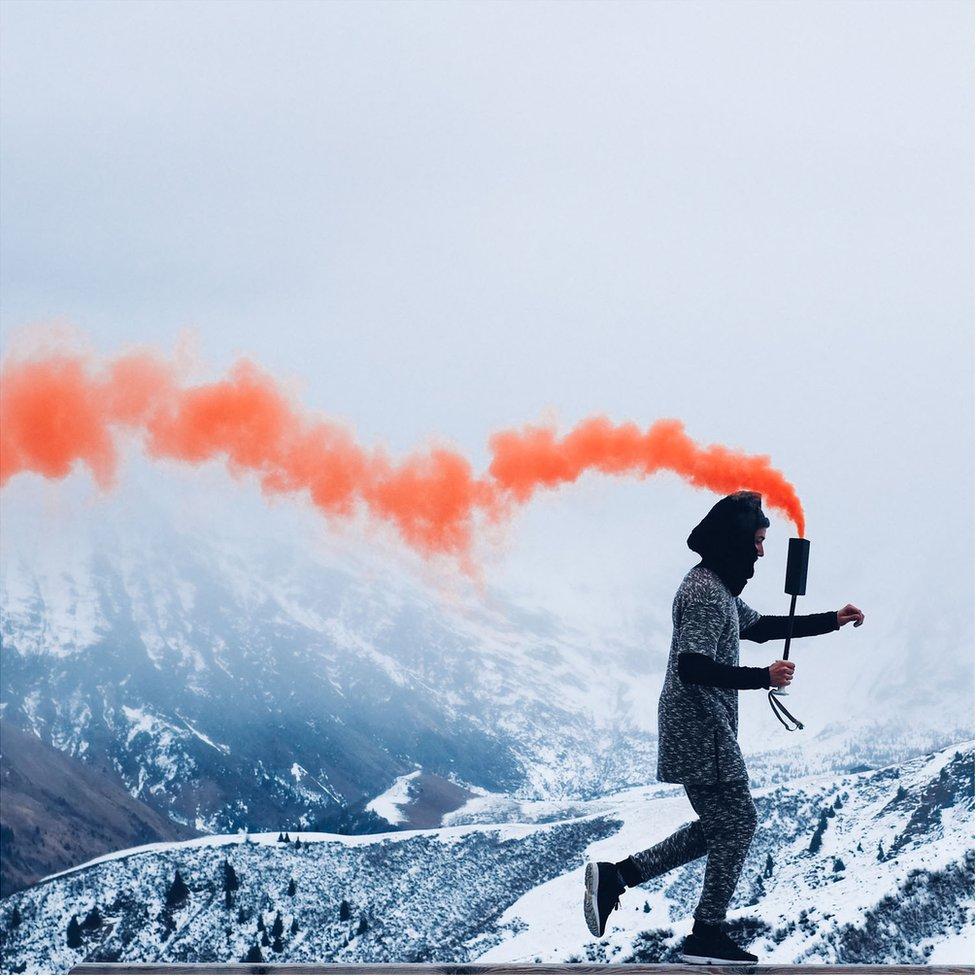 Man carrying plume of orange smoke