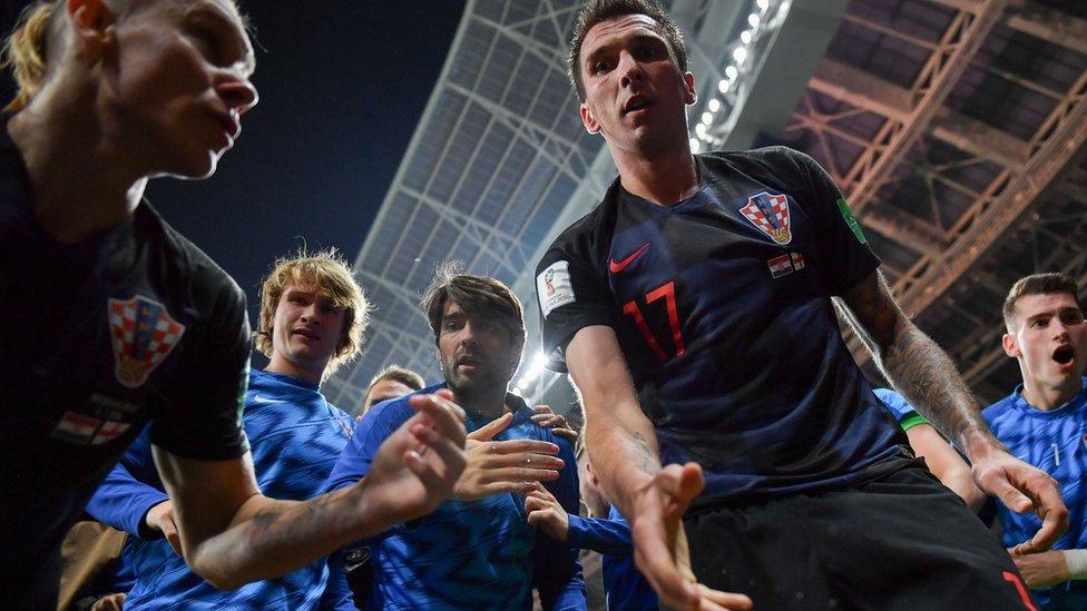 Miembros de la selección de Croacia ayudando a levantar del piso al fotógrafo Yuri Cortez