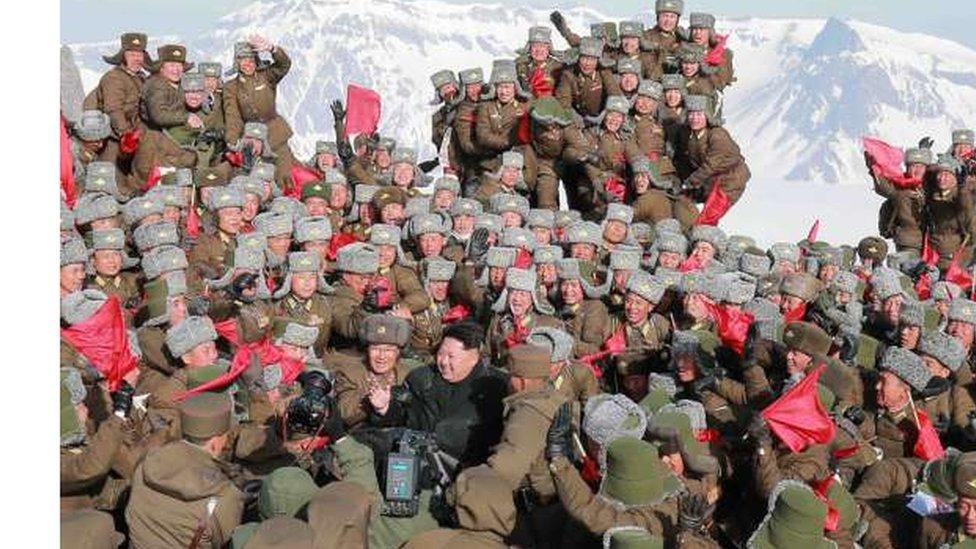 الزعيم الكوري الشمالي كيم جونغ أون في صورة التقطت على قمة جبل بايكتو وهو محاط بعدد كبير من الطيارين المقاتلين